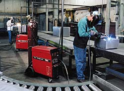 Operators manning four stations at the end of each automated production line weld the doors onto the enclosure.