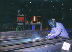 A welder uses one of several Lincoln CV-300 machines.